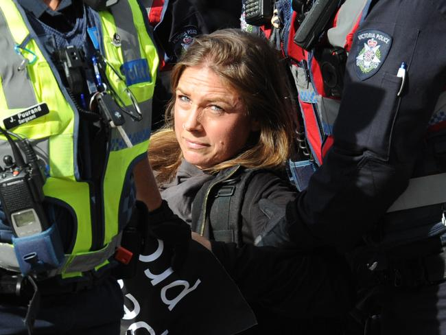 A woman is carried away by police. Picture: Andrew Henshaw