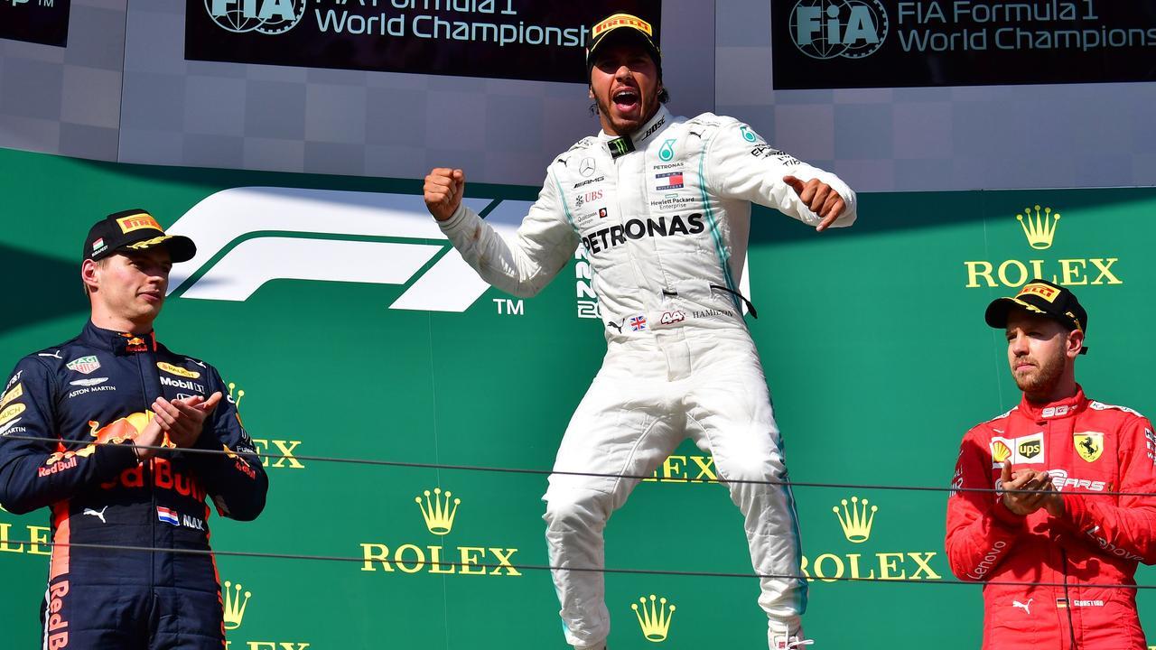 Verstappen and Vettel watch as Hamilton celebrates in Hungary. Picture: Andrej Isakovic
