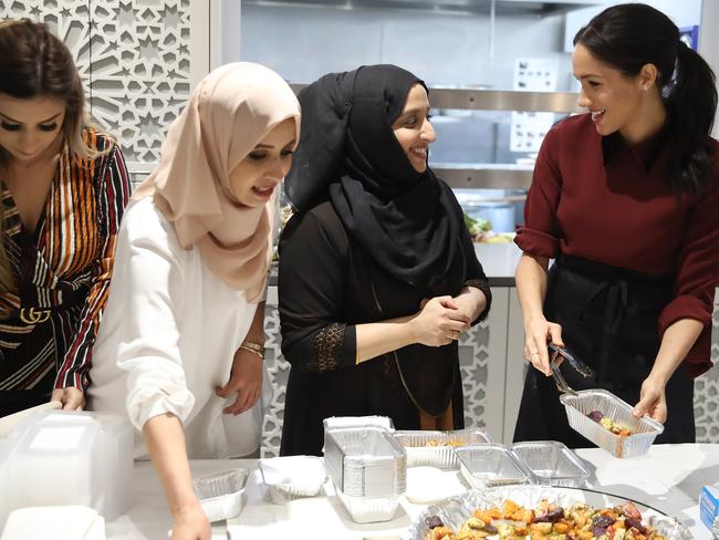 Meghan with some of the women who work at the community kitchen. Picture: Getty Images