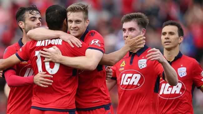 Adelaide United's Ryan Kitto (third from left) celebrates scoring with teammate Karim Matmour.