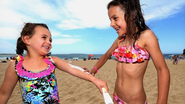 Abbie and Emily Seremetkoski putting on sunscreen at South Cronulla Beach.