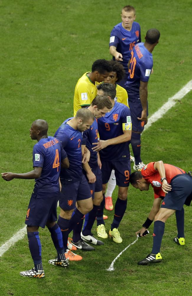 Referee Djamel Haimoudi from Algeria marks the spot for the Netherland's barrier.