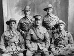 Outdoor portrait of five unidentified members of the AIF who enlisted as a group from Elder Smith & Co Ltd (Second Contingent). A L Elder & Co was established in Adelaide, SA in 1840, it had a number of name changes over the years, but was a wool and produce, brokerage and auctioneering business.