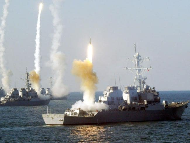 A group of Arleigh Burke Class Destroyers fire missiles during a training exercise. One of these ships will soon be fitted with the world's first operational laser cannon to go to sea. Picture: US Navy