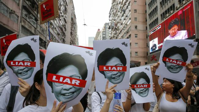 Protesters hold pictures of Hong Kong's leader Carrie Lam. Picture: AP Photo/Kin Cheung