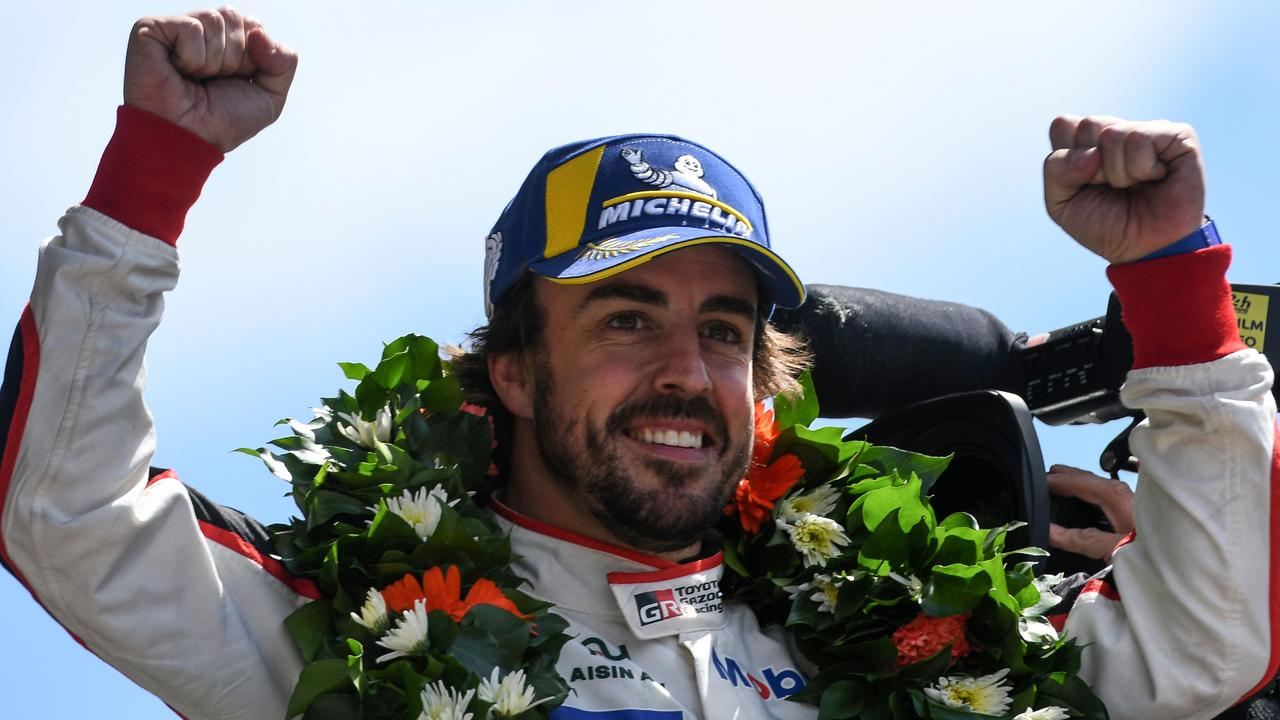 Fernando Alonso celebrates on the podium after he and his co-drivers won the 86th Le Mans 24-hours endurance race.