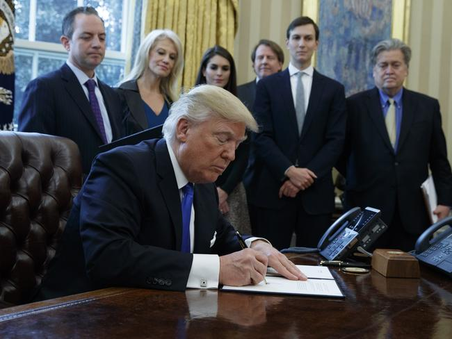 President Donald Trump signs an executive order on January 24 in the Oval Office of the White House in Washington. Picture: AP/Evan Vucci.