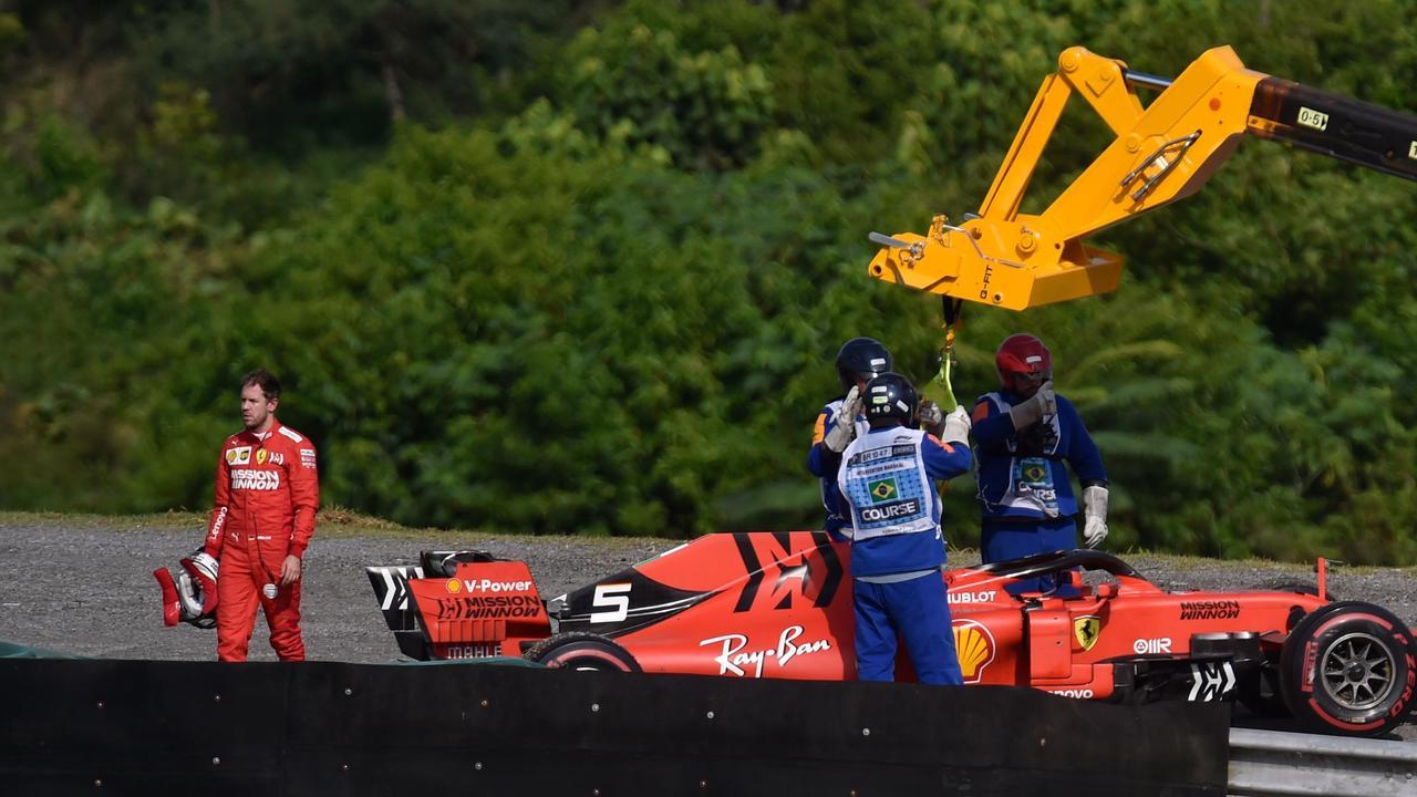 Sebastian Vettel reacts while a crane lifts his car. Picture: Douglas Magno