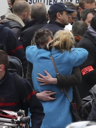 People hug each other outside Charlie Hebdo's office. Picture: Remy de la Mauviniere