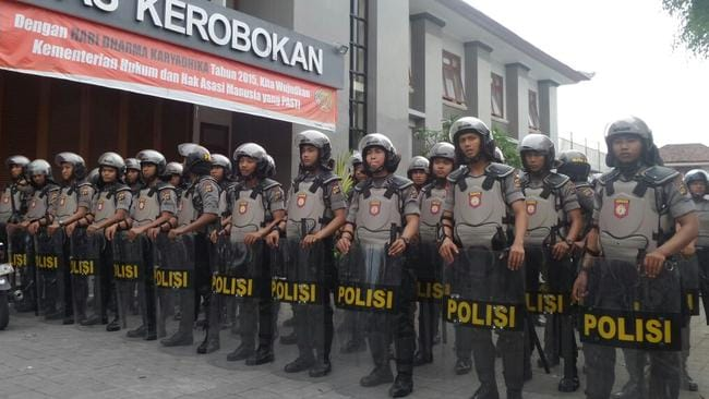Clashes ... the police riot squad at Kerobokan prison to quash the violence.