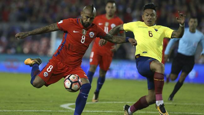 Chile's Arturo Vidal (L) fights for the ball against Ecuador's Cristian Ramirez.