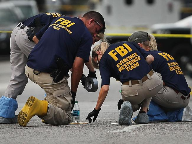 Members of an FBI evidence response team search an area that is still an active crime scene in downtown Dallas. Picture: Getty