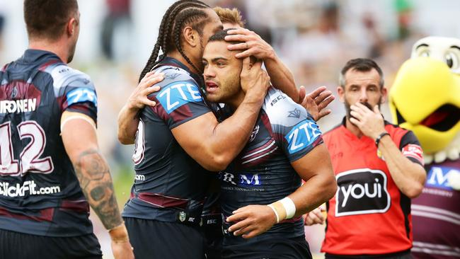 Dylan Walker of the Sea Eagles celebrates with teammates after scoring a try.