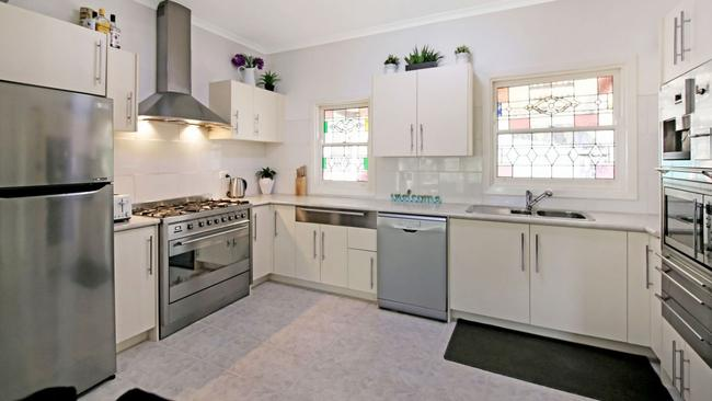 An updated kitchen still retains charming leadlight windows.