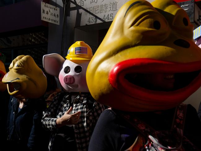 People wearing masks depicting 'LIHKG Pig' and Pepe the Frog, a character used by pro-democracy activists. Picture: AFP