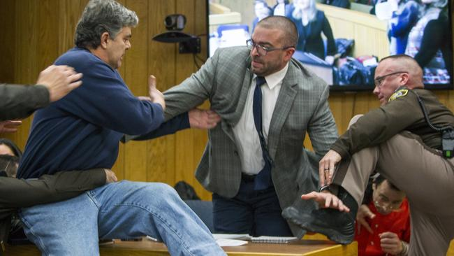 Randall Margraves, father of three victims, lunges at Larry Nassar (bottom right) in Eaton County Circuit Court in Charlotte, Michigan. Picture: Cory Morse/The Grand Rapids Press via AP