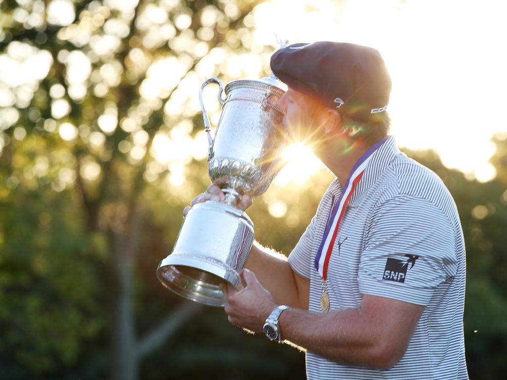 Bryson DeChambeau kisses the championship trophy. (Photo by Jamie Squire/Getty Images)