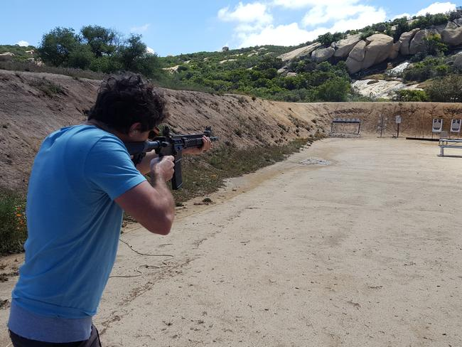 A reporter practices at a shooting range during 'situational awareness' training.