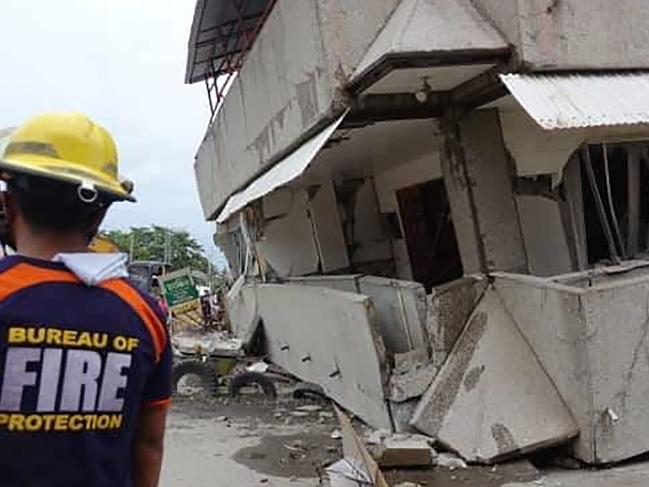 Rescuers after a strong quake jolted the southern Philippines causing a three-story building to collapse prompting people to rush out of shops and houses in panic. Picture: AP Photo
