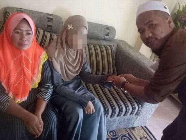 Malaysian national Che Abdul Karim, 41, poses with his latest wife Ayu, 11, (centre) and her mother (left) at a home in the Thai border village of Sugai Golok. Picture: Twitter