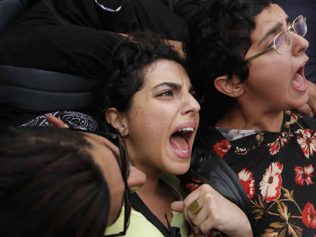 Anti-government protesters lie on a highway road, as they scream and hold each others after riot police arrive to remove them from the road, in Beirut. Picture: AP Photo/Hussein Malla