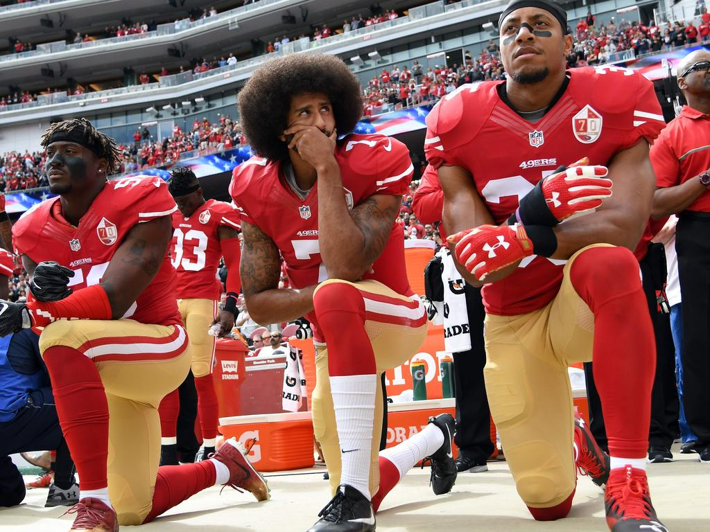 "(FILES) In this file photo taken on October 02, 2016 (L-R) Eli Harold #58, Colin Kaepernick #7 and Eric Reid #35 of the San Francisco 49ers kneel on the sideline during the anthem prior to the game against the Dallas Cowboys at Levi's Stadium in Santa Clara, California. - Former San Francisco 49ers quarterback Colin Kaepernick has been chosen as the face of a new Nike advertising campaign to mark the 30th anniversary of the company's iconic ""Just Do It"" slogan, it was confirmed on September 4, 2018. Kaepernick -- who triggered a political firestorm after kneeling during the US national anthem in 2016 to protest racial injustice -- has not played in the NFL since early last year.The 30-year-old is suing the NFL, claiming he has been frozen out of the league by team owners because of his activism. (Photo by Thearon W. Henderson / GETTY IMAGES NORTH AMERICA / AFP)"