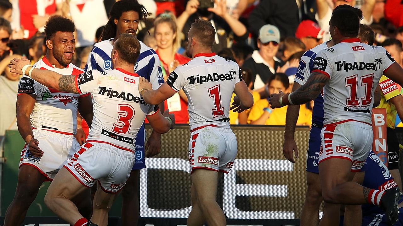 Mikaele Ravalawa of the Dragons celebrates with his teammates after scoring a try.