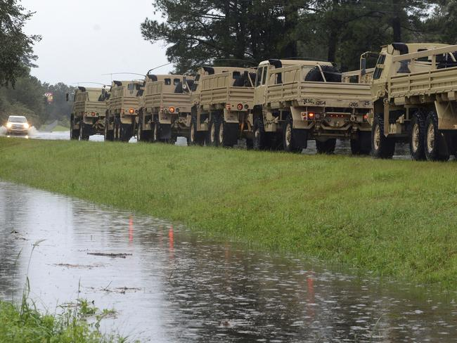 A line of military vehicles waits before driving through floodwaters rushing across US 70 East near the Lenoir County Shrine Club. Picture: AP