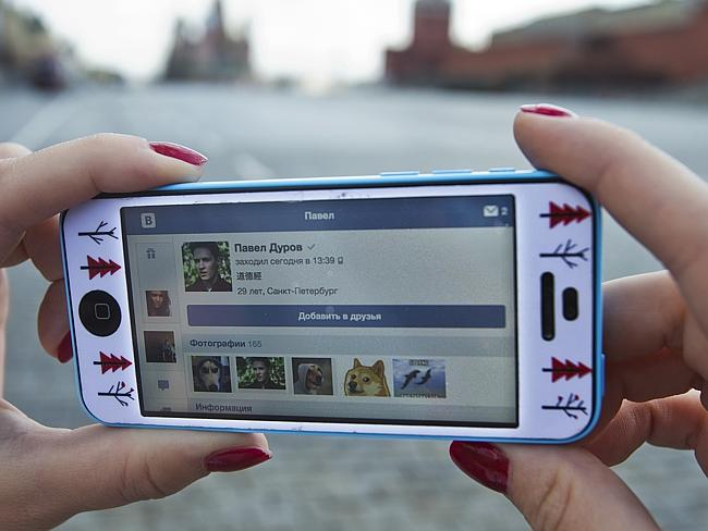 A user of Russia's leading social network internet site VKontakte, poses holding an iPhone showing the account page of Pavel Durov.
