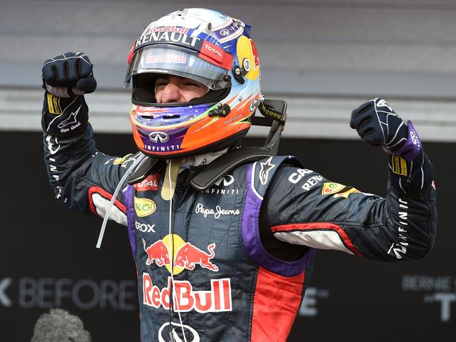 Daniel Ricciardo flexes his muscles after his late surge to win on the Hungaroring circuit in Budapest.