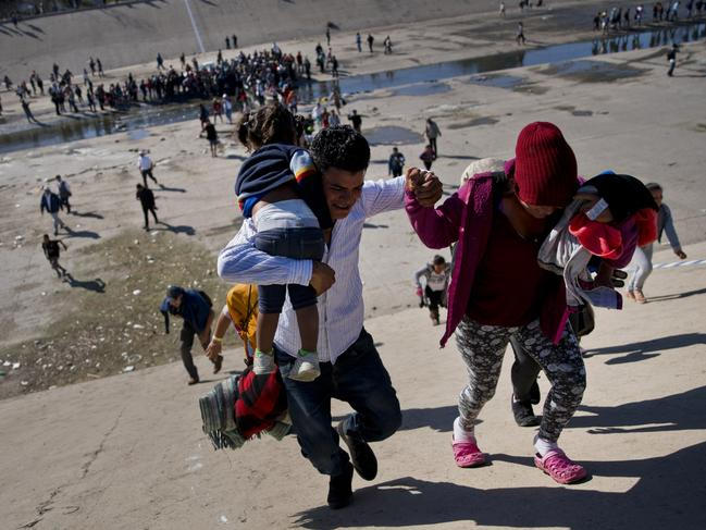 Migrants walk up a riverbank at the Mexico-U.S. border after pushing past a line of Mexican police at the Chaparral border crossing in Tijuana, Mexico, Sunday, Nov. 25, 2018, as they try to reach the U.S. Picture: AP Photo/Ramon Espinosa