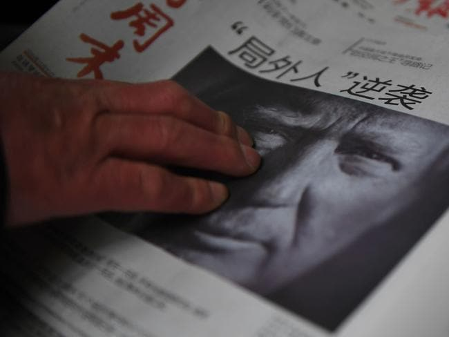 This file photo taken on November 10 shows a man buying a newspaper featuring a photo of US President-elect Donald Trump, the day after the US election. Picture: Greg Baker/AFP