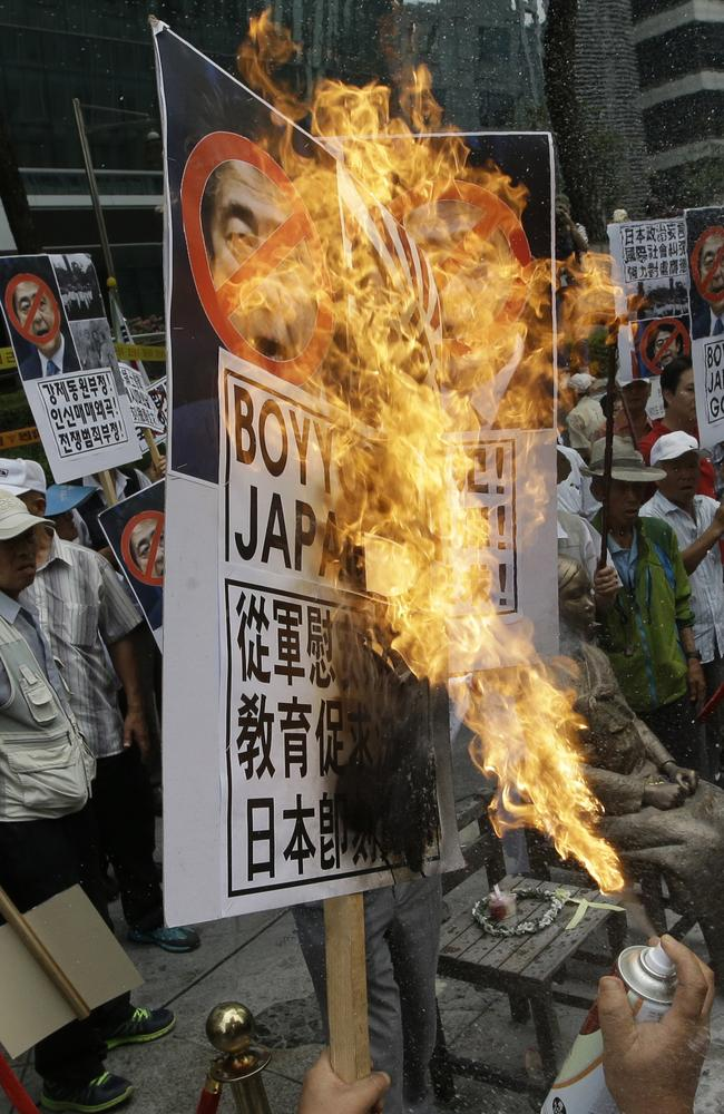 A South Korean protester ... burns defaced images of Japanese Prime Minister Shinzo Abe during a rally denouncing his statement to mark the 70th anniversary of the end of WWII. Picture: AP