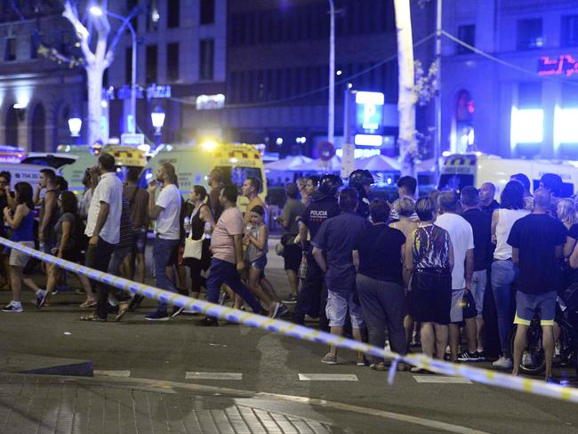 People gather to leave the cordoned off area after a van ploughed into the crowd on the Rambla in Barcelona. Picture: AFP