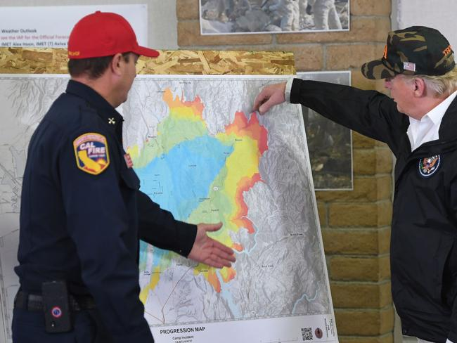US President Donald Trump looks at a map of the Camp fire and speaks with a fire fighter at Command Center Chico after viewing damage from wildfires. Picture: AFP