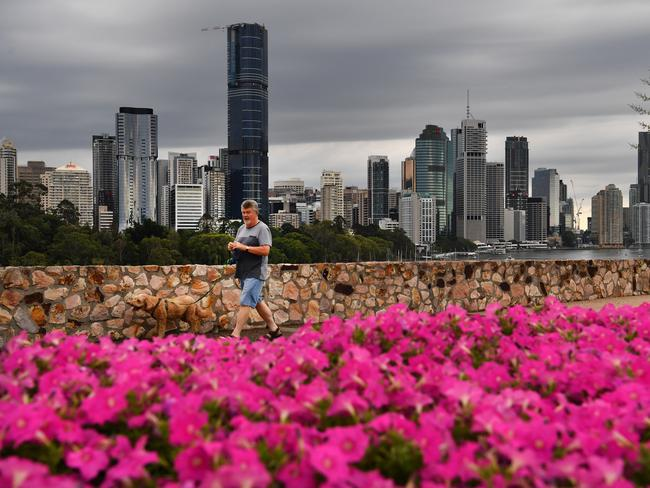 A man is seen walking his dog at the Kangaroo Point cliffs as storm clouds gather over the Brisbane CBD today. Picture: Darren England/AAP