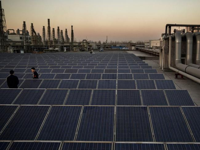 Technicians from Yingli Solar in Baoding walk among solar panels. Picture: Kevin Frayer/Getty Images