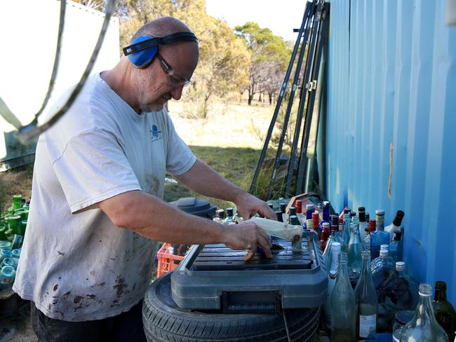 Mark cuts the tops of the beer bottles for his feature wall. Picture: Toby Zerna