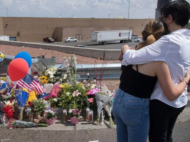 People hug beside a makeshift memorial outside the Cielo Vista Mall Walmart where a shooting left 22 people dead in El Paso, Texas. Picture: AFP