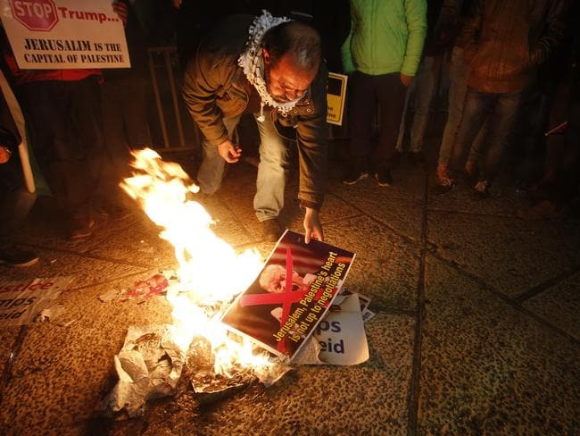 A Palestinian burns a poster of President Trump during a protest in Bethlehem, West Bank. Picture: AP