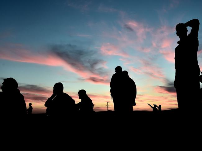 Attacks ... People watch air strikes on the Syrian town of Kobane. Picture: AFP