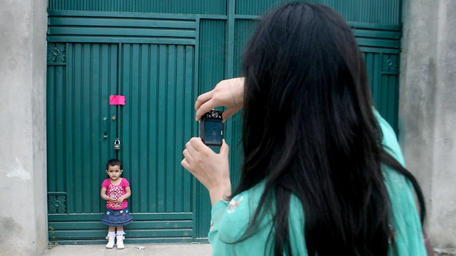 A Pakistani woman photographs her daughter at a gate of the compound where Osama bin Laden was killed. Picture: AP