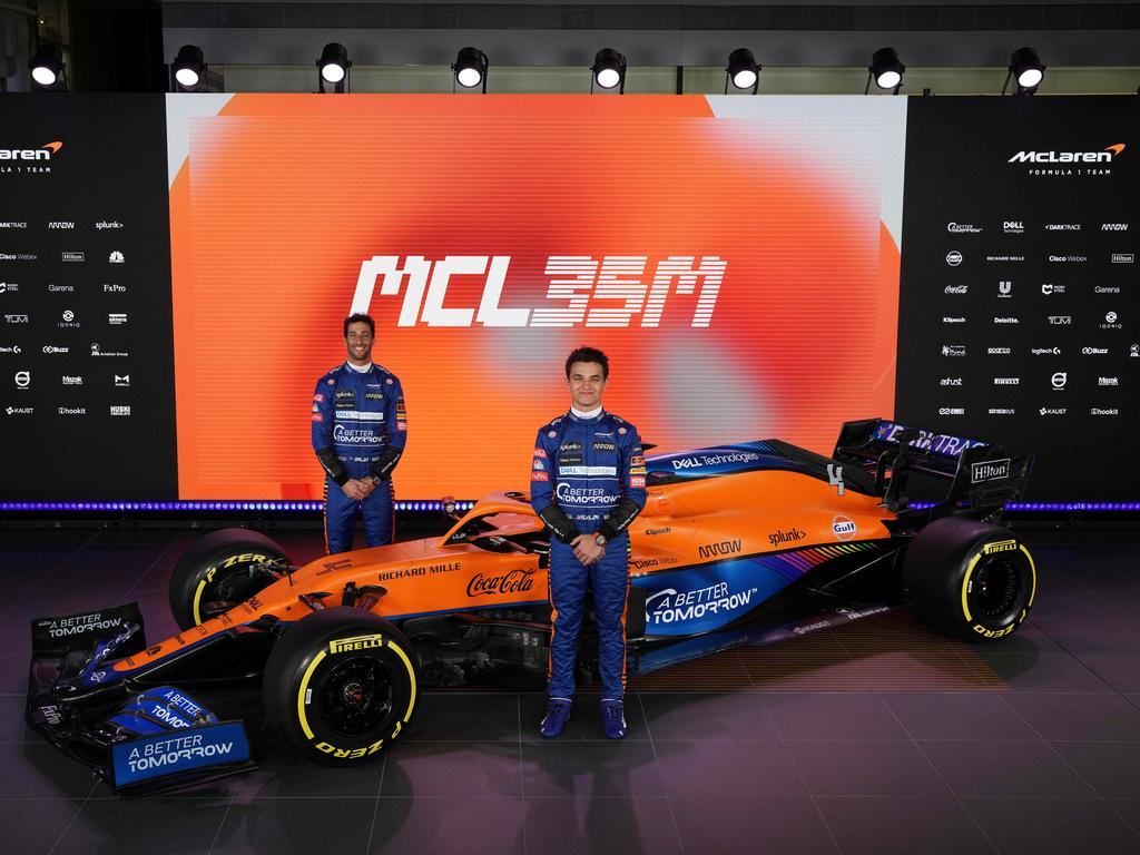 Lando Norris and Daniel Ricciardo posing by the new McLaren Formula 1 car MCL35M in Woking, southwest of London. (Photo by Handout / McLAREN / AFP)