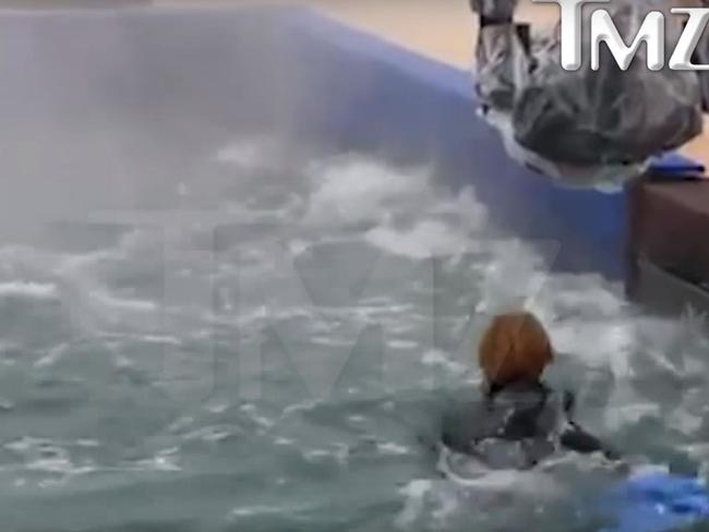 A woman races to rescue the dog straight after his head slips under the rushing water.