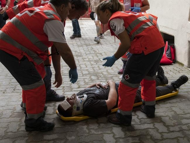 Medical staff take care of an injured reveller hurt during the annual running of the bulls festival in Pamplona, Spain. Picture: Getty
