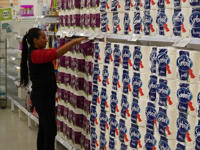 A Coles worker putting the final touches on restocking toilet paper. Picture: Coles