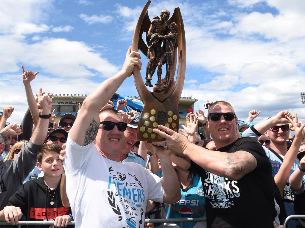 Cronulla Sharks captain Paul Gallen and forward Luke Lewis hold up the trophy at a fan day at Southern Cross Group Stadium, after they defeated the Melbourne Storm in the 2016 NRL Grand Final in Sydney, Monday, Oct. 3, 2016. (AAP Image/Mick Tsikas) NO ARCHIVING
