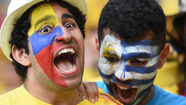 A Uruguayan supporter and Colombian doing their best 'Luis Suarez'.