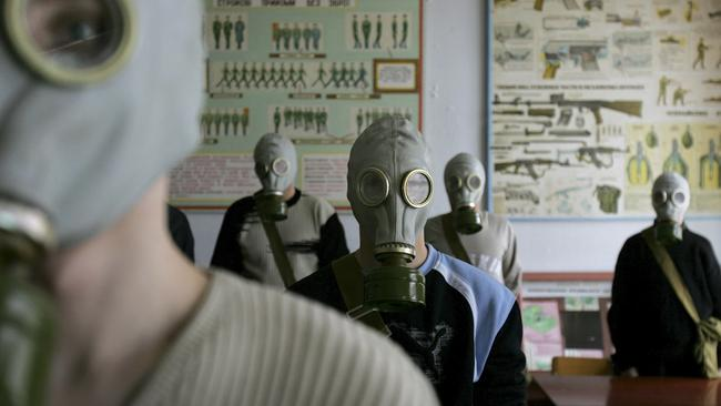 Ukrainian students try on gas masks as part of a safety drill in a school in Rudniya, just outside the Chernobyl contamination zone in 2006. Picture: Oded Balilty/AP