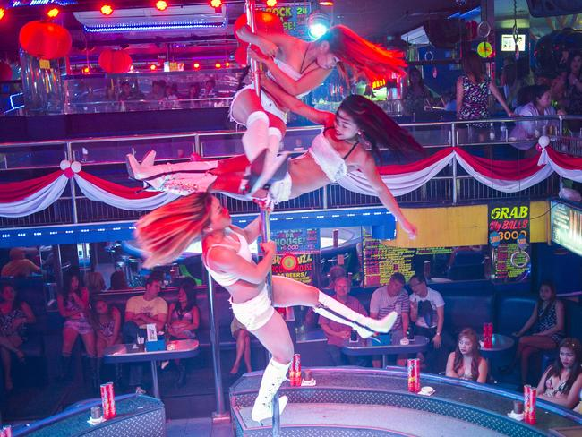 Pole dancers perform at 'Dolls House' go-go bar, one of the largest establishments on Fields Avenue. Picture: Dave Tacon.